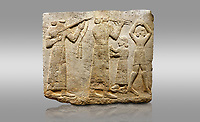 Picture & image of Hittite monumental relief sculpted orthostat stone panel of Procession. Limestone, Karkamıs, (Kargamıs), Carchemish (Karkemish), 900-700 B.C. Anatolian Civilisations Museum, Ankara, Turkey.<br /> <br /> Musicians. Two musicians with short arms, wearing long dresses and wide belts; one plays a Saz (a stringed musical instrument) with tassels on the handle while the other plays the flute. The third small figure holds castanets (?) in his hands. The figure on the right wears a short skirt, contrary to the others. She dances over her finger tips with her hands over her head. <br /> <br /> Against a gray background.