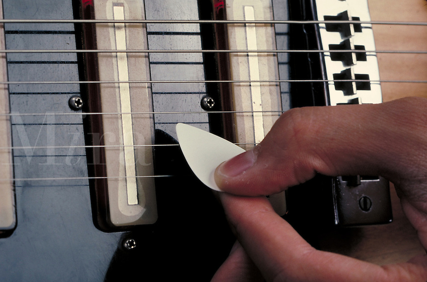 Plectrum, close-up of fingers, pick and guitar strings.  May not be used in an elementary school dictionary. Cleveland Ohio USA.