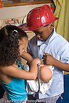 Preschool 4-5 year olds  pretend play boy and girl in dressup playing with doll together vertical