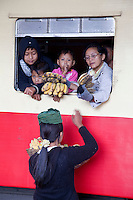 Myanmar, Burma.  Passengers in Coaches at Kalaw Train Station Bargaining with Banana Vendor.