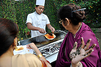 Women watch a chef cooking at the party before the wedding of British/Punjabi couple Lindsay and Navneet Singh.