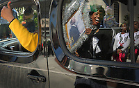 """Kelly.Jordan@jacksonville.com--011612--Veronica Price, of Jacksonville, is reflected in a window as she gets a """"thumbs up"""" from a passing parade float as she holds up her hand made tribute sign to Dr. Martin Luther King Jr. during the annual Martin Luther King Jr. Day parade through downtown Monday January 16, 2012.(The Florida Times-Union, Kelly Jordan)"""