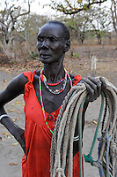 SOUTH-SUDAN Lakes State, Rumbek, village Colocok, Dinka woman in red dress with ropes in cattle camp / SUED SUDAN Rumbek, village Colocok, Dinka Frau mit Seilen ruer Kuehe im Cattle Camp