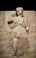 Roman Sebasteion relief sculpture of Ethnos with belted peplos, Aphrodisias Museum, Aphrodisias, Turkey.   Against a black background.<br /> <br /> The matronly figure wears a belted classical dress (peplos) and held her long cloak up behind. The square hole above her shoulder with a corresponding hole in the back, was for lifting the finished relief into the ancient building by crane.