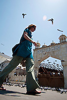 Female western tourist walking amongst the pigeons around entrance gate to Hazratbal Mosque, Srinagar, Kashmir, India.