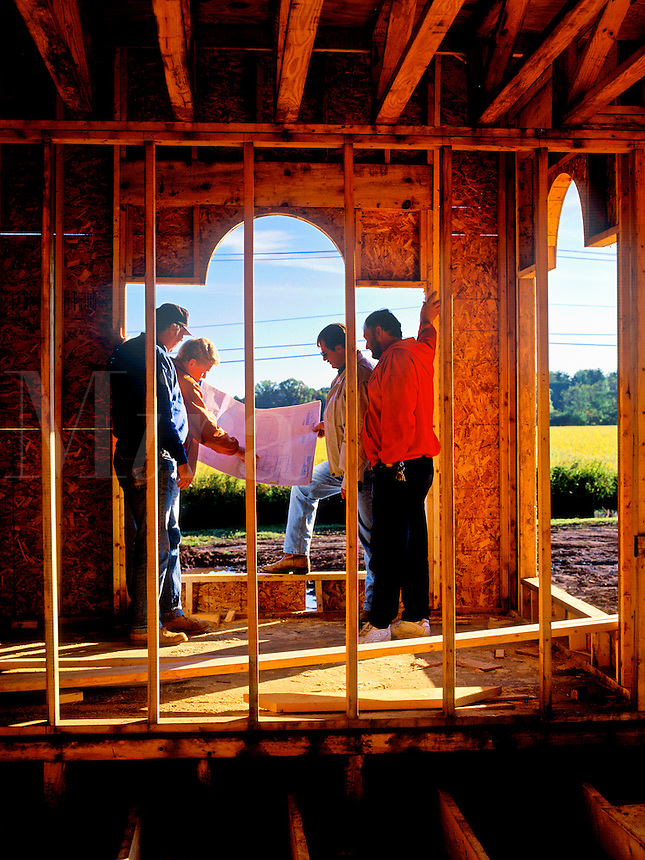 Worker review the schematic during the construction of a new house.