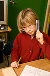 Education elementary Grade 3 science classroom male student doing experiment on sound production using tuning forks vertical