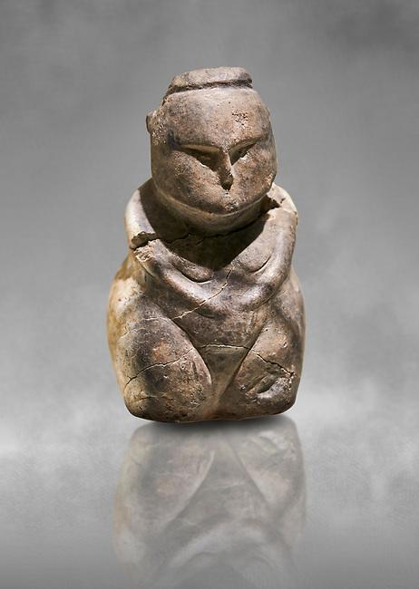 Styalised stone fiqurine. Catalhoyuk Collections. Museum of Anatolian Civilisations, Ankara. Against a gray mottled background