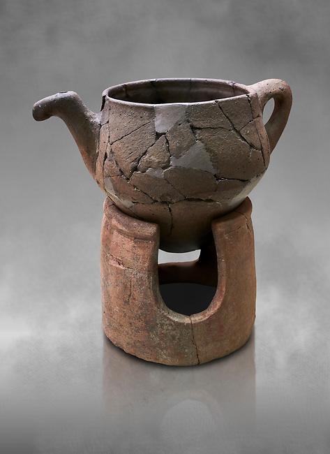 Hittite terra cotta teapot with strainer spout on a charcoa; burner base  . Hittite Period, 1600 - 1200 BC.  Hattusa Boğazkale. Çorum Archaeological Museum, Corum, Turkey. Against a grey bacground.