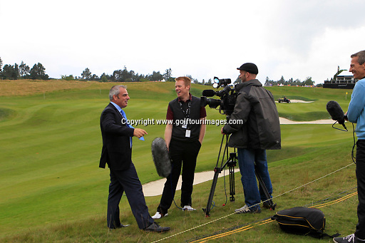 Paul McGinley takes a break from being interviewed by Phil Goodlad after a golf ball headed his way and a shout of fore ahead of the 2013 Johnnie Walker Championship being played over the PGA Centenary Course, Gleneagles, Perthshire from 22nd to 25th August 2013: Picture Stuart Adams www.golftourimages.com: 20th August 2013