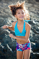 A young girl plays at a rocky North Shore beach on O'ahu.