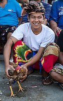 Bali, Indonesia.  Young Man with his Rooster Waiting for a Cock Fight in an Indonesian Village.