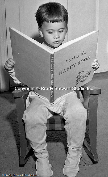 """Pleasant Hills PA:  Brady Stewart Studio participated in a national promotion for American Hardware Catalog Cover.  The contest asked for submissions to include a child reading a book at night time.  In this image, Cathleen Brady Stewart is reading """"The Great Big Happy Book""""."""
