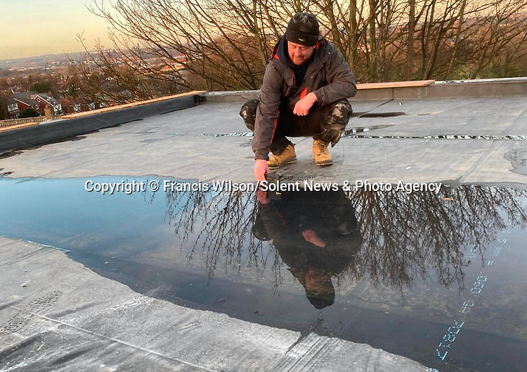 """Pictured:  Francis taking the photo using his mobile phone and the puddle.  <br /> <br /> Photos show the reflection of an extraordinary sunset reflected in a puddle - taken by a window fitter on his mobile phone.  Bare trees are seen in the orange sky beyond the roof where the snaps were taken by Francis Wilson, who only took up photography in March of this year.<br /> <br /> Despite his inexperience and lack of a digital camera, the 38 year old rushed to the roof of the house where he was working and captured the stunning photo on this week in Wakefield, West Yorks.  Mr Wilson, from nearby Huddersfield, said: """"Over the past few years I've got the latest phone, and I've always been quite creative.  SEE OUR COPY FOR DETAILS.<br /> <br /> Please byline: Francis Wilson/Solent News<br /> <br /> © Francis Wilson/Solent News & Photo Agency<br /> UK +44 (0) 2380 458800"""