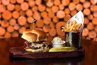 Still life photo of a specialty burger with fries.