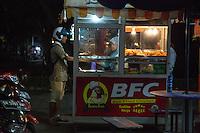 Jimbaran, Bali, Indonesia.  Young Man at a Bali Fried Chicken Stand, at Night.
