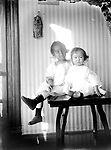 TABLETOP PORTRAIT<br /> A young girl and a toddler pose seated atop a shiny table. The bag pinned to the striped wallpaper may be Native American in origin.<br /> <br /> Photographs taken on black and white glass negatives by African American photographer(s) John Johnson and Earl McWilliams from 1910 to 1925 in Lincoln, Nebraska. Douglas Keister has 280 5x7 glass negatives taken by these photographers. Larger scans available on request.