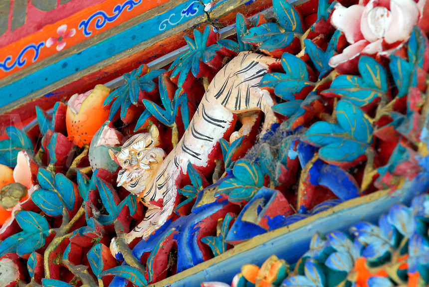 Carved detail of Tiger, one of four Dignities in Buddhist symbolism, represents confidence, in the entrance way to Takten Migyur Potrang, or New Summer Palace of the 14th Dalai Lama, at Norbulingka, founded by the 7th Dalai Lama in 1755, Lhasa, Tibet, China.
