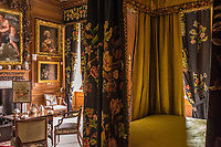 The wood-panelled walls of The Black and Yellow Bedroom are lined with gilt-framed masterpieces