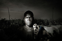 South Sudan. 23 March 2011...A young Dinka herdsman watches over his herd. The raids between different clans and tribes are very frequent, and herdsmen are often armed with Kalashnikovs..