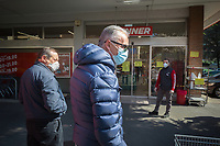 """Switzerland. Canton Ticino. Lugano. A worker stands at the entrance of Denner Supermarket. The man and various customers wear a mask on their faces to protect themselves from the Coronavirus (also called Covid-19). The worker's job is to control the door and and let enter only a restricted number of customers. Due to the spread of the coronavirus, the Federal Council has categorised the situation in the country as """"extraordinary"""". It has issued a recommendation to all citizens to stay at home, especially the sick and the elderly. The Federal Council (German: Bundesrat, French: Conseil fédéral, Italian: Consiglio federale, Romansh: Cussegl federal) is the seven-member executive council that constitutes the federal government of the Swiss Confederation. From March 16 the government ramped up its response to the widening pandemic, ordering the closure of bars, restaurants, sports facilities and cultural spaces. Only businesses providing essential goods to the population – such as grocery stores, bakeries and pharmacies – are to remain open. Denner is a discount supermarket chain in Switzerland. It is Switzerland's third largest supermarket chain with 11.4% market share. It is owned by the Federation of Migros Cooperatives since 2007. 17.03.2020 © 2020 Didier Ruef"""