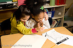 Elementary School New York Grade 2 two girls sharing a hug and a laugh while working together on social studies project horizontal