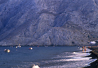 A couple strolls along the east shore of Santorini island.
