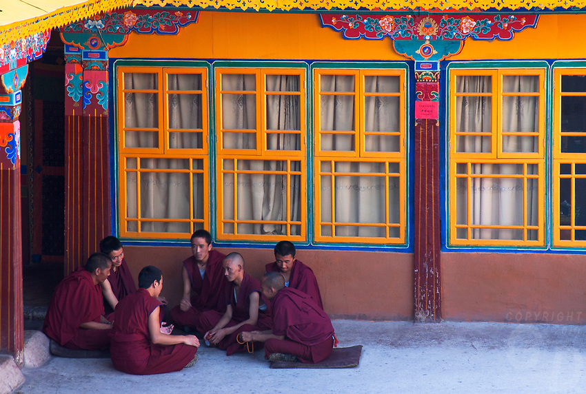 Debating Monks at The Jokhang also known as the Qoikang Monastery, Jokang, Jokhang Temple, Jokhang Monastery and Zuglagkang is a Buddhist temple inLhasa.Tibet<br /> Tibetans, in general, consider this temple as the most sacred and important temple in Tibet. The temple is currently maintained by the Gelung school, but they accept worshipers from all sects of Buddhism. The temple's architectural style is a mixture of Indian vihara, Tibetan and Nepalese design.<br /> The debate among monks unfolds in the presence of their teachers, with a very well set rules of procedure for the defender and the questioners. The tradition of such debates is traced to the ancient 'Hindu Orthodoxy' in India and this practice permeated into Buddhist orthodoxy in Tibet in the eighth century. <br /> <br /> Debates are punctuated with vigorous gestures which enliven the ambience of the occasion. Each gesture has a meaning. The debater presents his case with subtlety, robed in a formal monk's attire. Some of the gestures (said to have symbolic value), made during the debates, generally subtle dramatic gestures are: clapping after each question; holding right hand and stretching left hand forward and striking the left palm with the right palm; clapping hands loudly to stress the power and decisiveness of the defender's arguments denoting his self-assurance; in case of wrong answer presented by the defender, the opponent gestures three circles with his hand around the defenders head followed by loud screaming to unnerve the defender; opponent's mistake is demonstrated by wrapping his upper robe around his waist; loud clapping and intense verbal exchange is common; and the approach is to trap the defender into a wrong line of argument. Each time a new question is asked, the teacher strikes his outstretched left palm with his right palm. When a question is answered correctly, it is acknowledged by the teacher bringing the back of his right hand to his left palm.