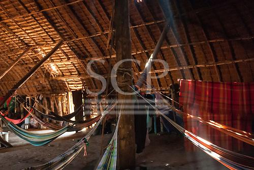 Xingu Indigenous Park, Mato Grosso, Brazil. Aldeia Matipu. Guest and family hammocks in traditional Oca house.