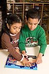 Education preschoool children ages 3-5 boy and girl working together on wooden puzzle vertical