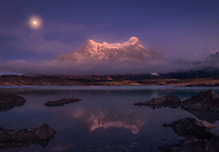 The setting moon and impending sunrise illuminate Paine Grande on a foggy morning in Patagonia.