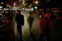 People walk through a street market in the city center of Shaoxing, Zhejiang, China.  The smoke is from street vendors barbecuing food.