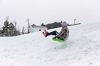 Sunny Souv (CQ) sleds over a small make shifts snow jump with friends Monday February 15, 2021, on a hill behind the First Presbyterian Early Learning Center in Rogers.  <br /> (NWA Democrat-Gazette/Spencer Tirey)