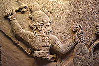 Picture & Image of  Neo-Hittite orthostat describing the legend of Gilgamesh from Karkamis,, Turkey. To the left a bearded deity with a horned helmet is holding a lions back leg and is about to strike it with an axe. To the right a man is stabbing the lion with a dagger. An Ankara Museum of Anatolian Civilizations exhibit.