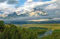 Scenic landscape of the Snake River Overlook - a wide green prairie with the Grand Teton Mountains surrounded by cloud in the background. Jackson Hole, Wyoming.
