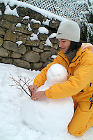 Mother making a snowman for her children, Selonnet, French Alps, France.