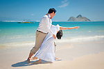 Asian bride and groom dance and dip while they stroll on Lanikai beach as they look forward to their life as a married couple following their wedding.