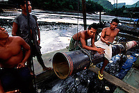 Missile dredge operators in a tributary of the Essequibo, Guyana.  Missile dredges dig up the river bottom and shoot it out the back over vibrating tables in a search for gold.  There are no regulations for this activity and it is an ecological nightmare.