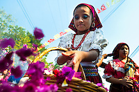 """A Salvadoran girl throws colorful flower blooms during the procession of the Flower & Palm Festival in Panchimalco, El Salvador, 8 May 2011. On the first Sunday of May, the small town of Panchimalco, lying close to San Salvador, celebrates its two patron saints with a spectacular festivity, known as """"Fiesta de las Flores y Palmas"""". The origin of this event comes from pre-Columbian Maya culture and used to commemorate the start of the rainy season. Women strip the palm branches and skewer flower blooms on them to create large colorful decoration. In the afternoon procession, lead by a male dance group performing a religious dance-drama inspired by the Spanish Reconquest, large altars adorned with flowers are slowly carried by women, dressed in typical costumes, through the steep streets of the town."""