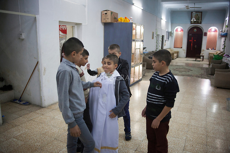 16/11/14. Alqosh, Iraq. Milad tries on the robes, to show his friends, that he wears when serving as an alter boy during Sunday services.