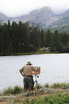 Caucasian senior citizen painting a landscape of Hallet Peak from Sprague Lake in Rocky Mountain National Park, Estes Park, Colorado. .  John offers private photo tours in Denver, Boulder and throughout Colorado. Year-round.