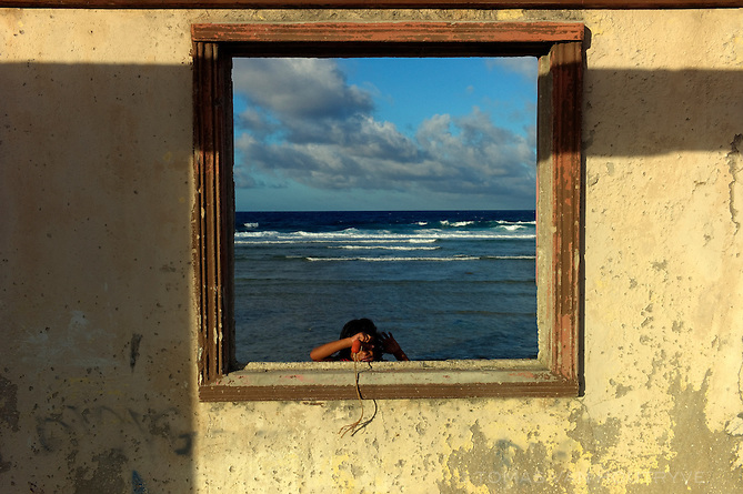 A child looks through the window frame of a partially destroyed abandoned home on the Pacific shore of Ebeye, Marshall Islands on June 16, 2012. Over 12,000 people live on the tiny overcrowded island of 36 hectares. The islanders relocated to Ebeye from their original homes because the U.S. military leases those areas for ballistic missile testing. Other current residents of Ebeye moved from islands which were contaminated by U.S. nuclear bomb tests. Infrastructure, housing and sanitation on Ebeye are deplorable.