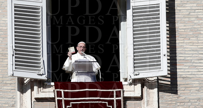 """Papa Francesco, durante la preghiera dell'Angelus in Piazza San Pietro, mostra un libro intitolato """"Icone di Misericordia"""" che verrà distribuito ai fedeli. Città del Vaticano. 6 gennaio 2017.<br /> Pope Francis shows a booklet, titled """"Icons of Mercy"""" that will be distributed to faithful, during the Angelus prayer from his studio's window overlooking St. Peter's square, at the Vatican, on January 6, 2017.<br /> UPDATE IMAGES PRESS/Isabella Bonotto<br /> <br /> STRICTLY ONLY FOR EDITORIAL USE"""