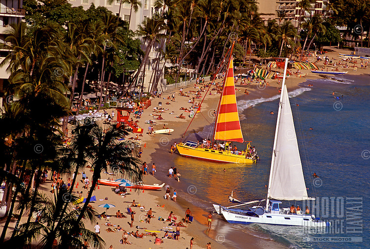 Crowds of tourists enjoy relaxing on beautiful Waikiki beach with two large catamarans on the shoreline.