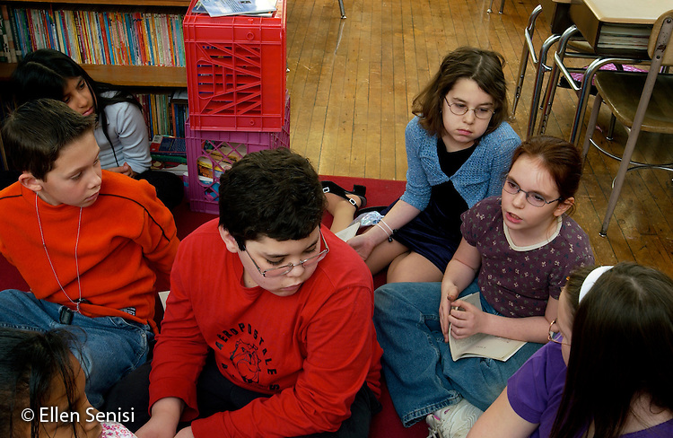 MR / Schenectady, NY.Yates Arts-in-Education Magnet School (urban elementary school) .Grade 4 .Student speaks during class discussion on social issues using literature as starting point. Teacher and class members take turns reading aloud from The Night the Bells Rang (Natalie Kinsey Warnock) and then discussing the theme: bullying and harassment both in the book and in their personal experiences. .MR: g4m  .© Ellen B. Senisi