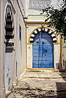 Tunisia, Sidi Bou Said.  Blue Door to Private Home, Black and White Stone Arch.   The high door knockers date from the time when guests arrived on horseback.