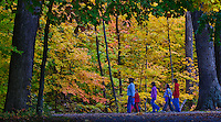 Mother and children walk through a park in the fall.