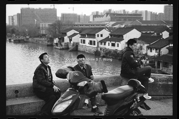 Local residents rest on a stone bridge over the ancient Beijing-Hangzhou Grand Canal in Hangzhou, Zhejiang province, China, March 2013.