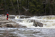 Kayaker studies the Lower Falls on the Swift River during the spring months in the White Mountains, New Hampshire USA.