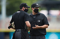 Umpire Macon Hammond brings baseballs to home plate umpire Zee Zdenek during the game between the Carolina Mudcats and the Kannapolis Cannon Ballers at Atrium Health Ballpark on June 13, 2021 in Kannapolis, North Carolina. (Brian Westerholt/Four Seam Images)